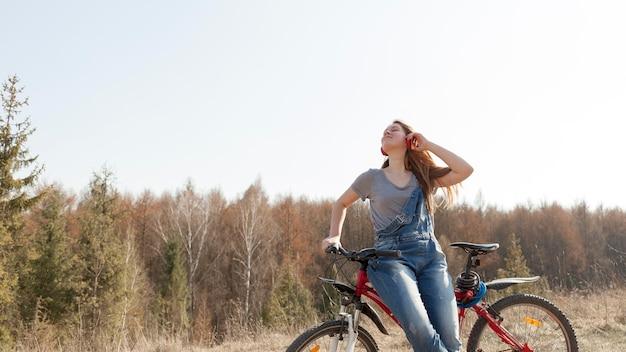 Vista frontal da mulher despreocupada com fones de ouvido em bicicleta na natureza