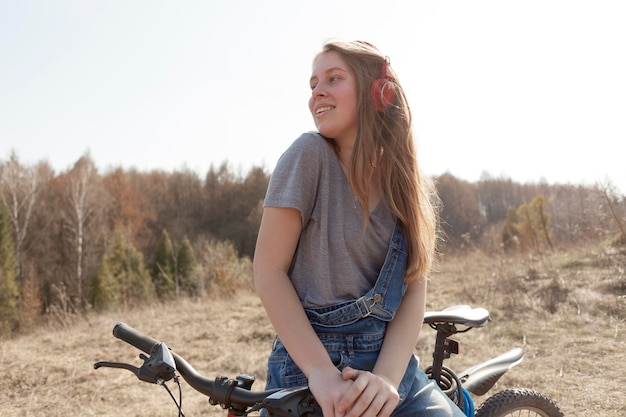 Vista frontal da mulher despreocupada em bicicleta na natureza