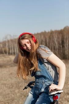 Vista frontal da mulher despreocupada, ouvindo música em bicicleta na natureza