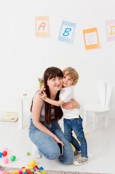 Vista frontal da mulher e menino posando juntos em casa