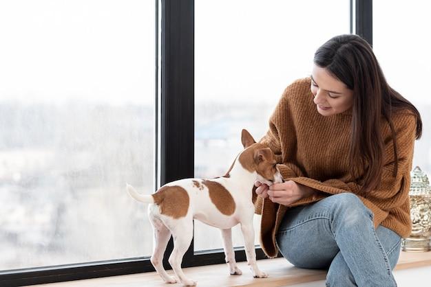 Vista frontal da mulher e seu cachorro com espaço de cópia