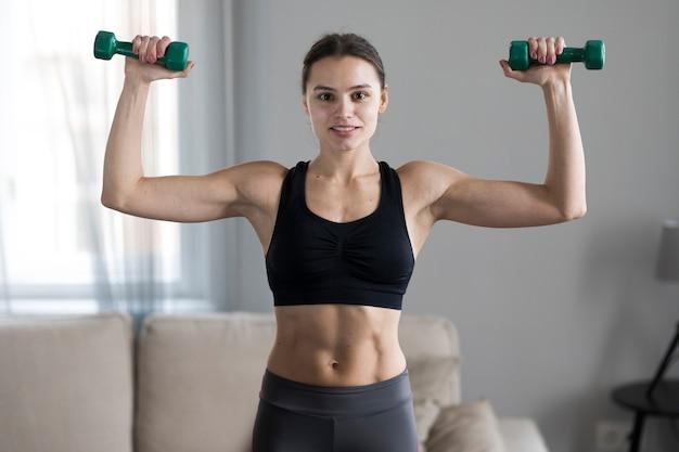 Vista frontal da mulher em athleisure levantando pesos