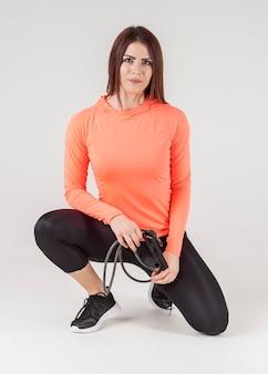 Vista frontal da mulher em athleisure posando enquanto segura a banda de resistência