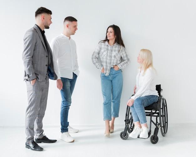 Vista frontal da mulher em cadeira de rodas, conversando com seus colegas de trabalho