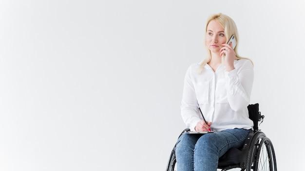 Vista frontal da mulher em cadeira de rodas, falando ao telefone