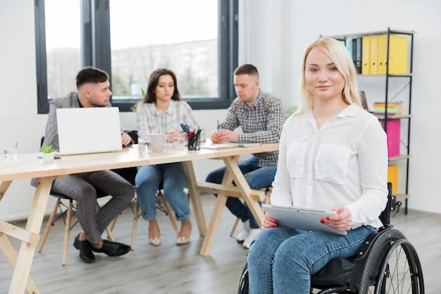 Vista frontal da mulher em cadeira de rodas, posando no escritório