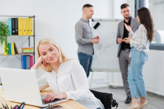 Vista frontal da mulher em cadeira de rodas, posando no trabalho enquanto colegas conversam