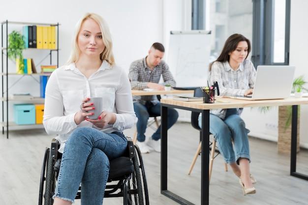 Vista frontal da mulher em cadeira de rodas, posando no trabalho, mantendo a caneca