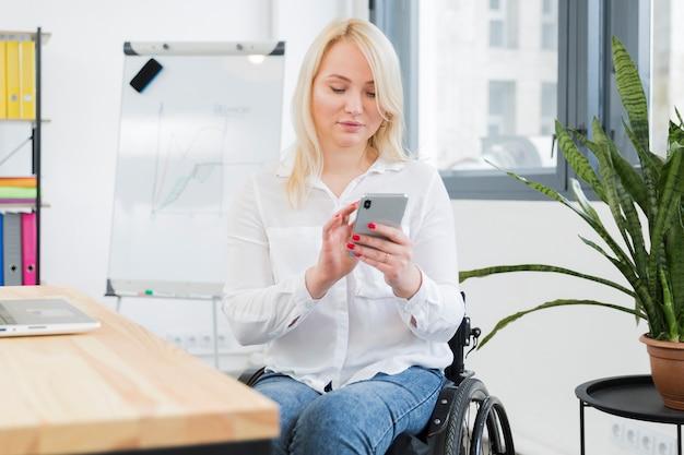 Vista frontal da mulher em cadeira de rodas, segurando o smartphone