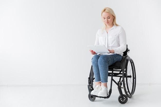 Vista frontal da mulher em cadeira de rodas, segurando o tablet