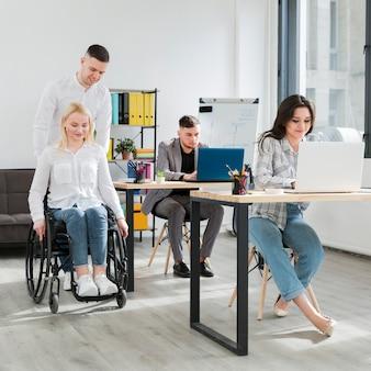 Vista frontal da mulher em cadeira de rodas, sendo ajudada pelo colega de trabalho no escritório