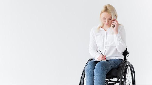 Vista frontal da mulher em cadeira de rodas, trabalhando e falando ao telefone