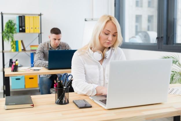 Vista frontal da mulher em cadeira de rodas, trabalhando em sua mesa no escritório