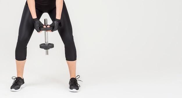 Vista frontal da mulher em trajes de ginástica, segurando o peso