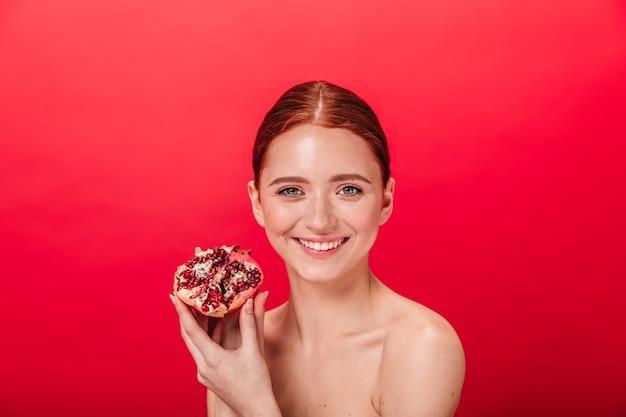 Vista frontal da mulher encantadora, sorrindo e segurando granada suculenta. foto de estúdio de despreocupada menina ruiva com romã.