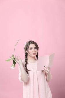 Vista frontal da mulher entediada segurando rosa e livro