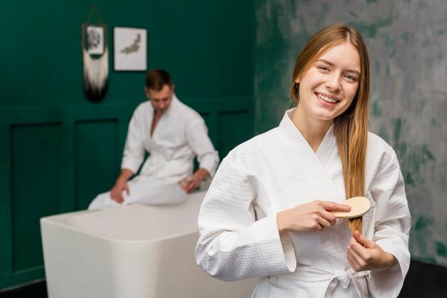 Vista frontal da mulher escovar os cabelos com homem em roupão