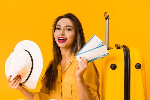 Vista frontal da mulher excitada segurando bilhetes de avião