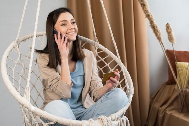 Vista frontal da mulher falando no smartphone e segurando o cartão de crédito