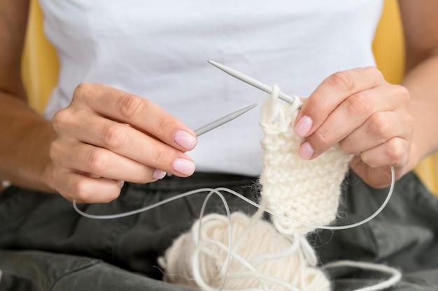 Vista frontal da mulher fazendo crochê