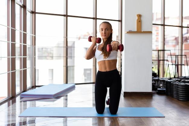Vista frontal da mulher fazendo musculação