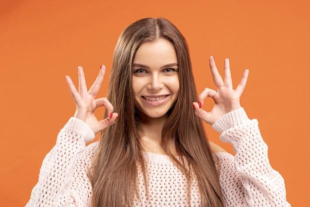 Vista frontal da mulher fazendo sinal de ok com ambas as mãos