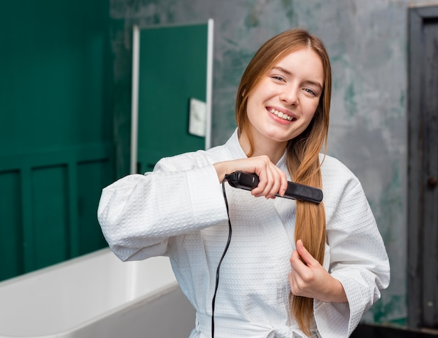 Vista frontal da mulher feliz, alisar o cabelo