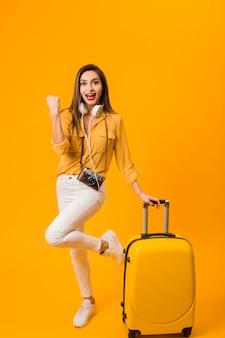 Vista frontal da mulher feliz ao lado de bagagem