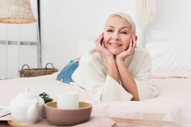 Vista frontal da mulher feliz madura, sorrindo e posando na cama