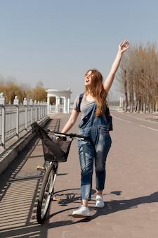Vista frontal da mulher feliz, se aquecendo ao sol enquanto caminhava ao lado de bicicleta
