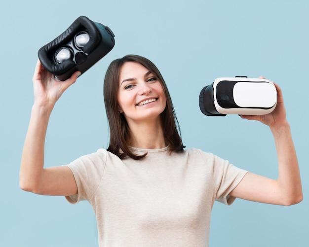 Vista frontal da mulher feliz, segurando o fone de ouvido da realidade virtual