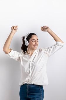 Vista frontal da mulher feliz usando fones de ouvido