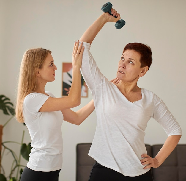 Vista frontal da mulher idosa em recuperação cobiçosa fazendo exercícios com a enfermeira e halteres