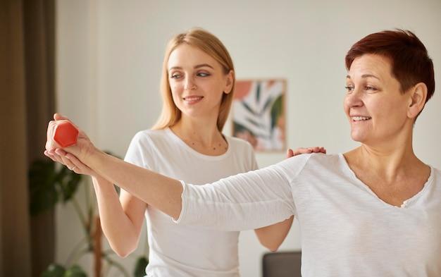 Vista frontal da mulher idosa em recuperação cobiçosa fazendo exercícios com halteres e enfermeira