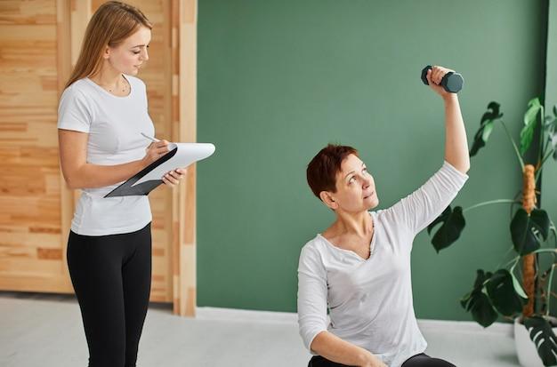 Vista frontal da mulher idosa em recuperação cobiçosa, fazendo exercícios físicos com halteres enquanto a enfermeira verifica