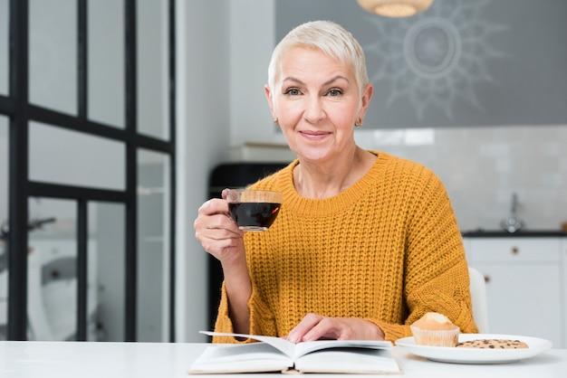 Vista frontal da mulher idosa segurando a xícara de café