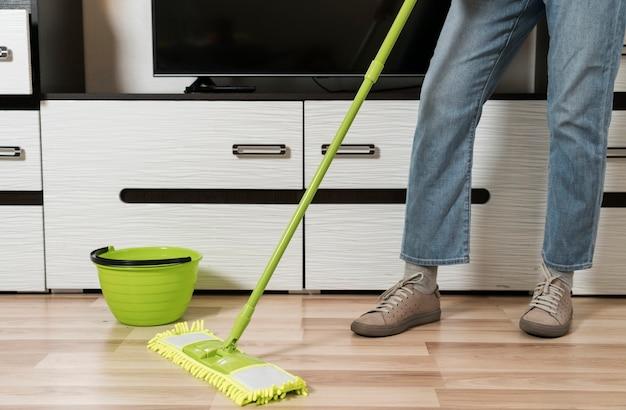 Vista frontal da mulher limpando o chão