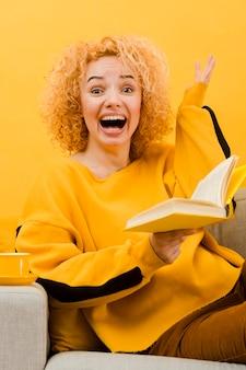 Vista frontal da mulher loira lendo um livro