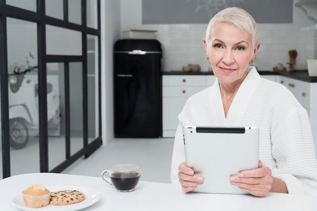 Vista frontal da mulher madura em roupão segurando o tablet