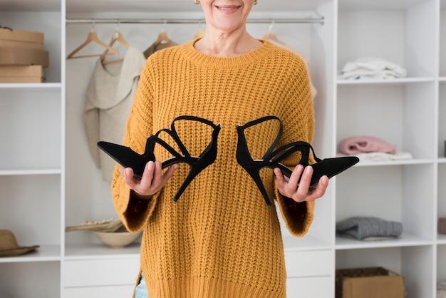 Vista frontal da mulher madura, sorrindo e segurando o par de sapatos nas mãos