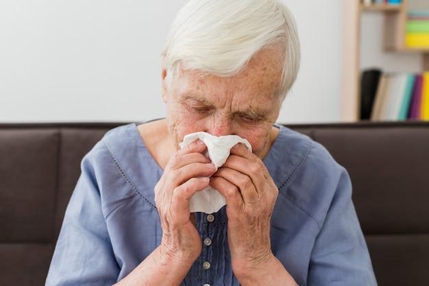 Vista frontal da mulher mais velha assoar o nariz em guardanapo