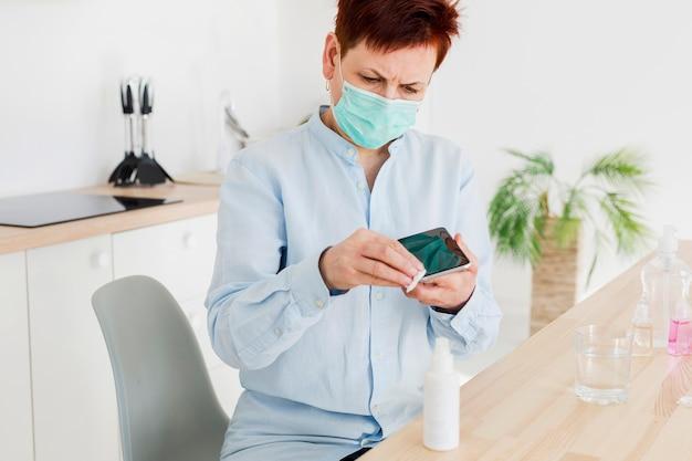 Vista frontal da mulher mais velha, higienizando seu smartphone