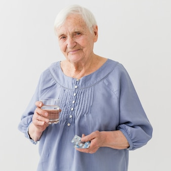Vista frontal da mulher mais velha, segurando seus comprimidos