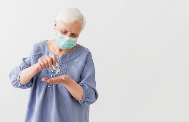 Vista frontal da mulher mais velha, usando desinfetante para as mãos, com espaço de cópia