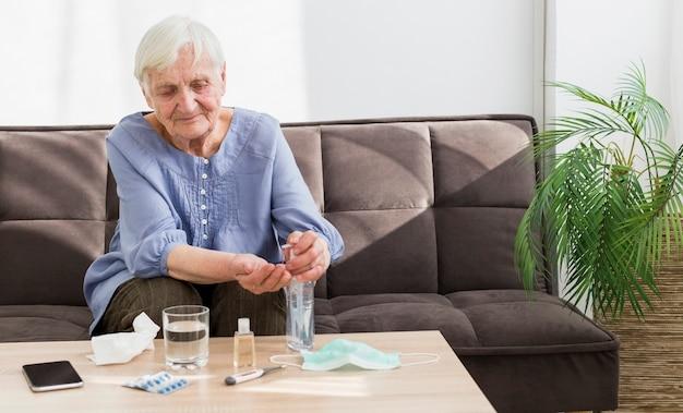 Vista frontal da mulher mais velha usando desinfetante para as mãos em casa