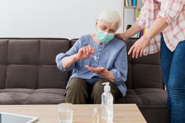Vista frontal da mulher mais velha usando desinfetante para as mãos enquanto usava máscara médica