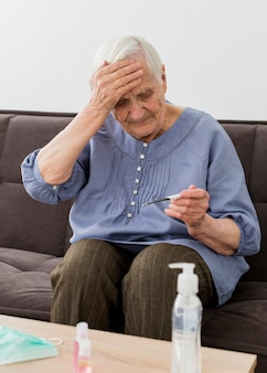 Vista frontal da mulher mais velha, verificando seu termômetro