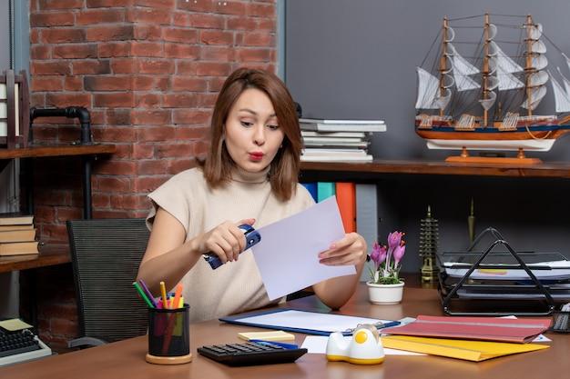 Vista frontal da mulher maravilhada usando grampeador sentada no escritório