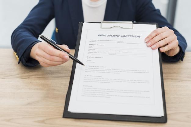 Vista frontal da mulher mostrando onde assinar novo contrato