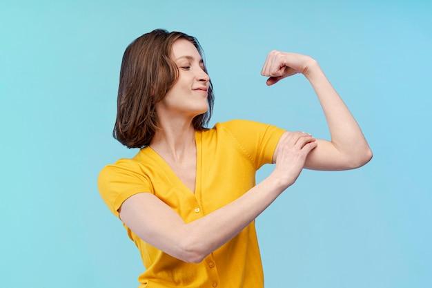 Vista frontal da mulher mostrando seu bíceps forte